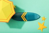 top view of paper yellow umbrella near starfishes and surfboard on turquoise background