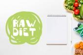 Draufsicht auf leeres Notizbuch in der Nähe von Diätfutter und Springseil auf weißem Hintergrund mit rohem Diätschriftzug