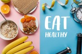 top view of fresh fruits, crispbread and breakfast cereal on pink and dumbbells and measuring tape on blue background with eat healthy lettering