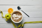 top view of measuring tape, spoon and breakfast cereal in bowl near apple and orange on wooden white background with breakfast always fresh lettering