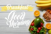 top view of fresh fruits, vegetables in heart-shaped bowl on wooden white background with breakfast, good morning lettering