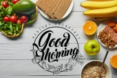 top view of fresh fruits, vegetables and cereal on wooden white background with healthy breakfast, good morning illustration