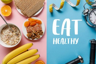 Top view of fresh fruits, crispbread and breakfast cereal on pink and dumbbells and measuring tape on blue background with eat healthy lettering stock vector