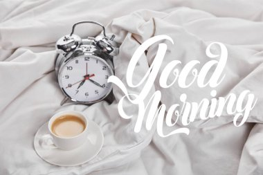 coffee in white cup on saucer near silver alarm clock in bed with good morning illustration