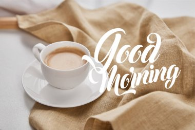 close up view of coffee in white cup on saucer near beige napkin with good morning illustration
