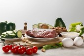 fresh raw meat on wooden chopping board near nuts and vegetables isolated on grey, ketogenic diet menu