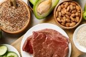 pohled na čerstvé syrové maso na bílém plechu v blízkosti ořechů, krupice a avokáda, ketogenní jídelníček