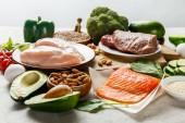 surový losos, maso a kuřecí prsa v blízkosti zelené zeleniny, izolované na šedé, ketogenní jídelníček