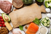 top view of raw salmon, chicken breasts and meat near nuts, dairy products and vegetables around wooden chopping board with copy space, ketogenic diet menu