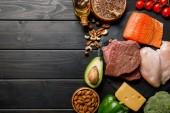 pohled na čerstvý surový losos, maso a kuřecí prsa na dřevěném černém stolku se zeleninou a ořechy, ketogenní jídelníček