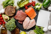 top view of blank notebook near raw meat and fish among fresh vegetables, ketogenic diet menu