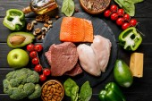 vista dallalto di salmone crudo, carne e petto di pollo su tavolo nero di legno con verdure e noci, menu di dieta chetogenica