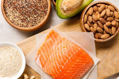 Top view of fresh raw salmon on wooden chopping board near nuts, groats and avocado, ketogenic diet menu stock vector