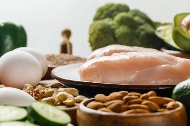 selective focus of raw chicken breasts and eggs isolated on grey, ketogenic diet menu