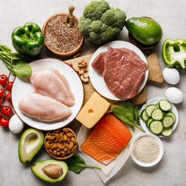 top view of raw ketogenic diet ingredients on wooden chopping board on grey background with copy space