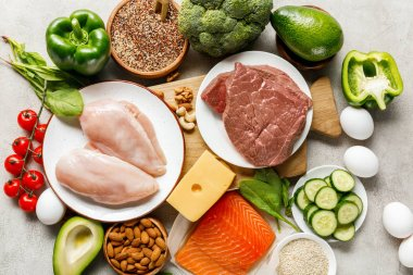 top view of raw fresh ketogenic diet ingredients on wooden chopping board on grey background with copy space