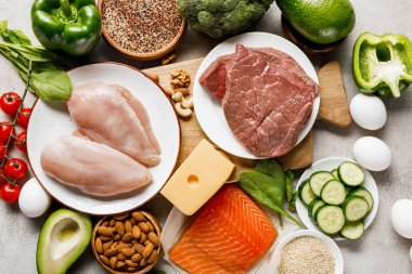 top view of raw organic ketogenic diet ingredients on wooden chopping board on grey background with copy space