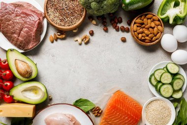 top view of raw salmon, chicken breasts and meat near nuts, dairy products and vegetables on grey background with copy space, ketogenic diet menu