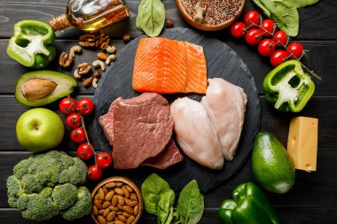 top view of raw salmon, meat and chicken breasts on wooden black table with vegetables and nuts, ketogenic diet menu