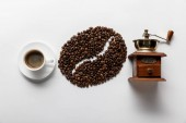 top view of coffee grain, cup of coffee and retro coffee grinder on white background