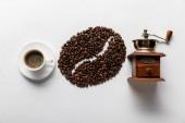 pohled na kávové zrno, šálek kávy a mlýnek na kávu na bílém pozadí