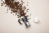 top view of metal coffee pot, cup and scattered fresh coffee beans on beige background