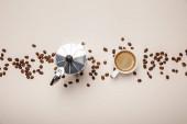 pohled na kovovou kávovou konvici, kávovou fazoli a šálek na béžové pozadí