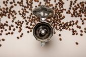 pohled na otevřený kovový kávový hrnec s čerstvou kávou v blízkosti kávových bobů na béžové pozadí