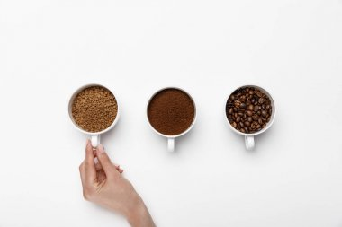 cropped view of female hand near three types of coffee grinding in cups on white background