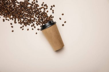top view of coffee to go and scattered fresh coffee beans on beige background