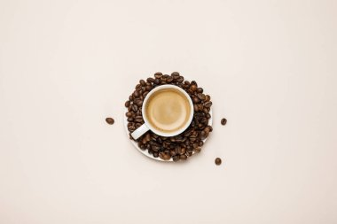 top view of cup with delicious coffee on coffee grains on beige background