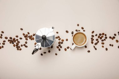 top view of metal coffee pot, coffee beans and cup on beige background