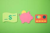 lapos feküdt malacka bank, hitelkártya-és dolláros bankjegy izolált zöld
