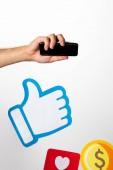 oříznutý pohled člověka přidržením smartphone nad barevným papírem ikony s mincí, srdcem a palcem nahoru na bílém pozadí