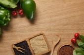 pohled na bílou, červenou a černou chinoi v miskách blízko zralé zeleniny a lžíce na dřevěném stole