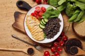 Top-Ansicht der gekochten Quinoa mit gegrillter Hähnchenbrust und Gemüse auf weißem Teller auf Holz-Schneidebrett