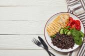Blick von oben auf gekochte Quinoa mit gegrillter Hühnerbrust und Gemüse auf weißem Holztisch mit Besteck und Serviette