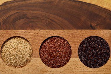top view of white, black and red quinoa in wooden round bowls