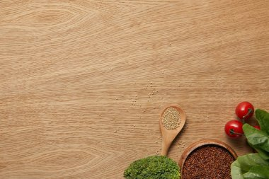 top view of white and red quinoa in wooden bowl and spoon near vegetables