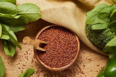 top view of red quinoa in wooden bowl with spatula near beige napkin and green vegetables