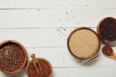 top view of white, black and red quinoa seeds in wooden bowls on white textured table