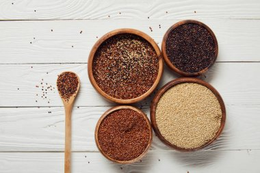 top view of white, black and red quinoa in wooden bowls near spoon on white table
