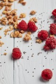 Photo selective focus of scattered raspberries, chia seeds and oat flakes on white wooden table
