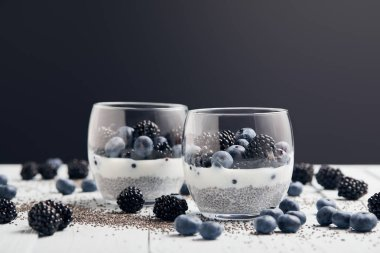 selective focus of yogurt with chia seeds and berries in glasses near scattered seeds, blueberries and blackberries on white table isolated on black