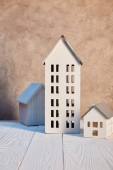 houses models on white wooden table near textured wall, real estate concept