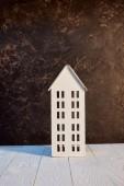 model domu na bílém dřevěném stole blízko hnědé texturované zdi, koncepce realit