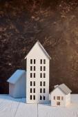 modelli case su tavolo di legno bianco vicino parete marrone strutturato, concetto immobiliare