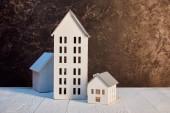házak modellek fehér fából készült asztal közelében, barna textúrájú fal, ingatlan koncepció