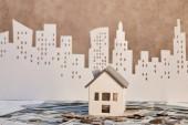 model domu na dolarových bankovkách v blízkosti mincí a papírového města na pozadí, koncept nemovitostí