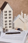 houses models on white wooden table with contract, keys and coins, real estate concept
